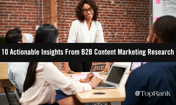 Professional black women leading group of fellow B2B marketers around table image.